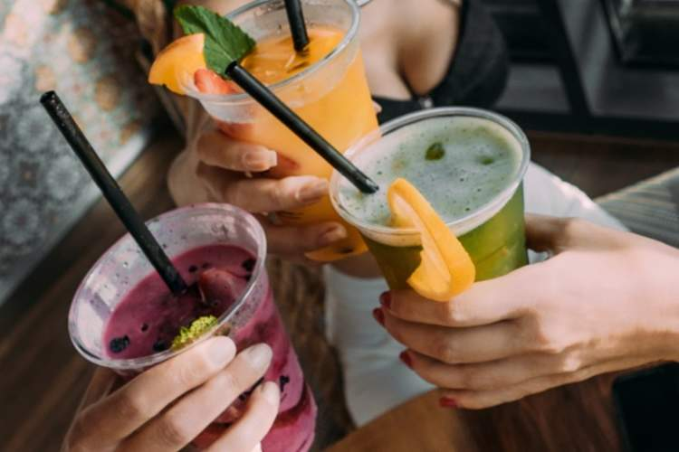 group of women cheers-ing with smoothies