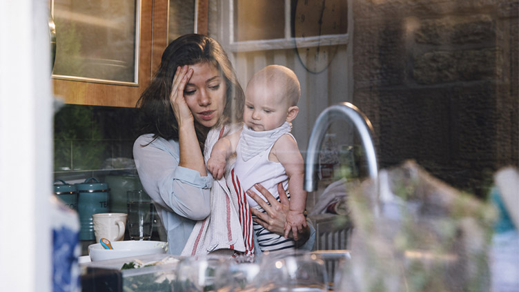 Stressed young mother at home with baby in kitchen.