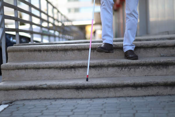 man with white support cane walking down the stair