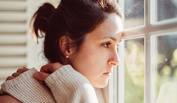 depressed woman looking out window image