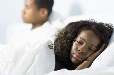 Woman sleeping while partner watches television image.
