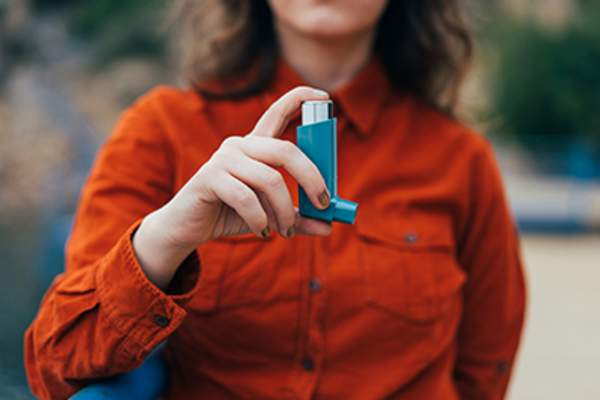 Woman holding an inhaler.