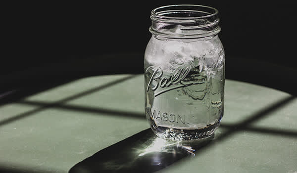 Water with ice in a glass jar.