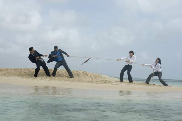 Multi-ethnic businesspeople having tug of war
