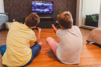 Two boys playing video game, sitting on floor in living room.