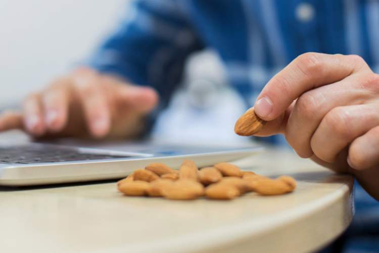 Man snacking on almonds while working on computer.