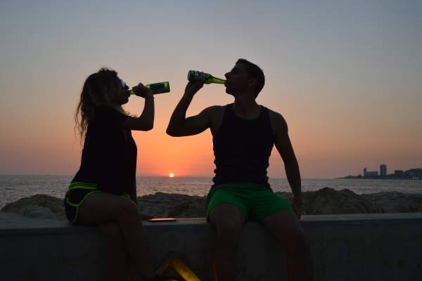 couple drinking beer on beach at sunset