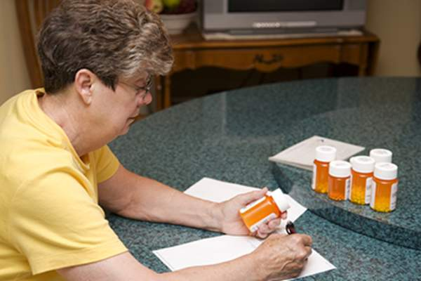 Senior woman making list of medications.