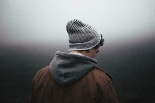 Depressed man in hat looking away