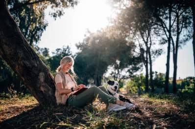 senior woman sitting under tree with dog