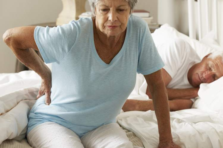 A woman with spinal stenosis back pain gets out of bed.