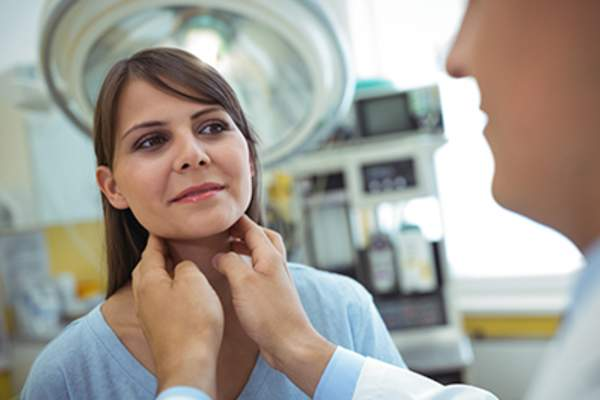 Woman getting a thyroid exam from a doctor.
