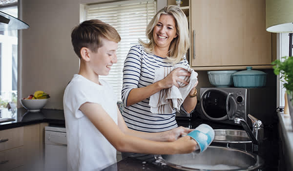 Child washing dishes with his mother.