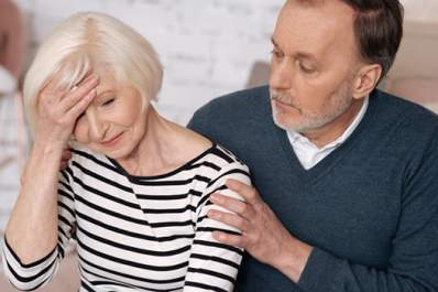 Man supporting stressed woman with headache.