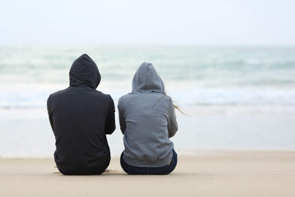 Man and Woman sitting solemnly at beach