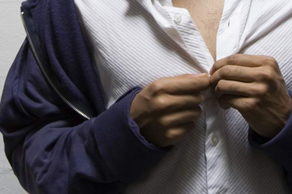 Woman having trouble buttoning her blouse.