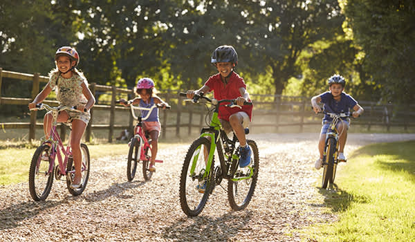 Children riding bikes together in the summer.