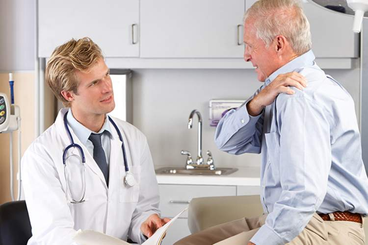 Patient explaining shoulder pain to a doctor.