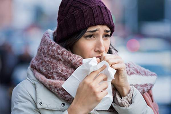 Woman outdoors with a cold.