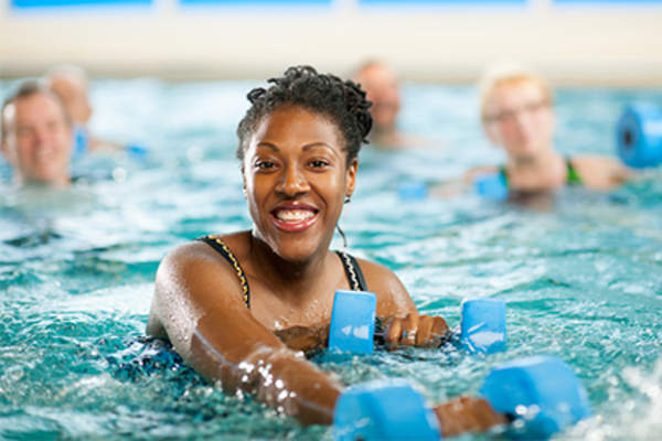 Smiling woman in water aerobics class.