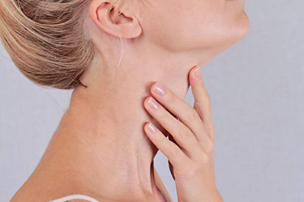Woman touching her thyroid glands.