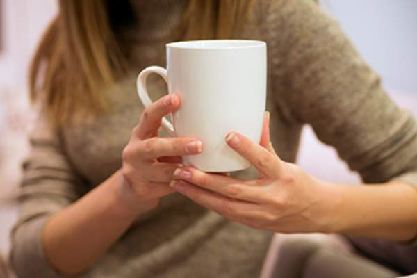 Woman holding white cup of coffee or tea