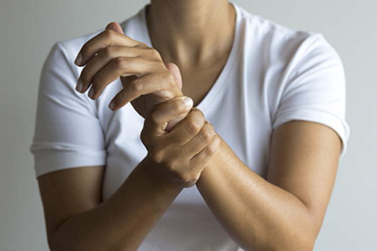 A woman holds her wrist with RA joint pain.