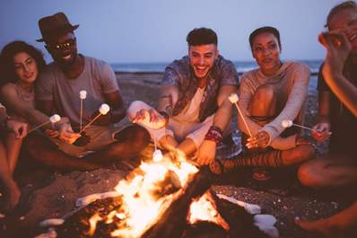 Friends toasting marshmallows at the beach.