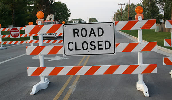 Road closed sign with other blockades in the background.