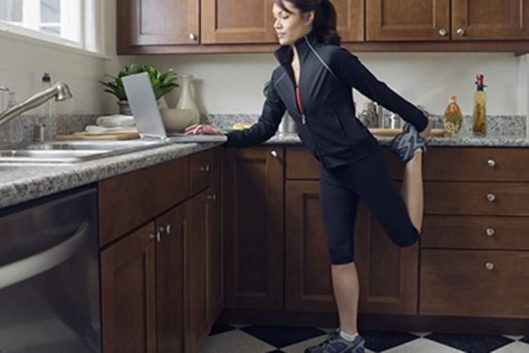 A woman stretches in her kitchen while looking at her laptop.