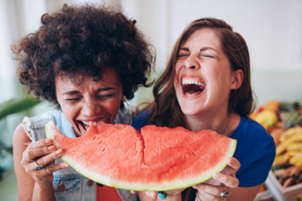 Women laughing and eating watermelon together