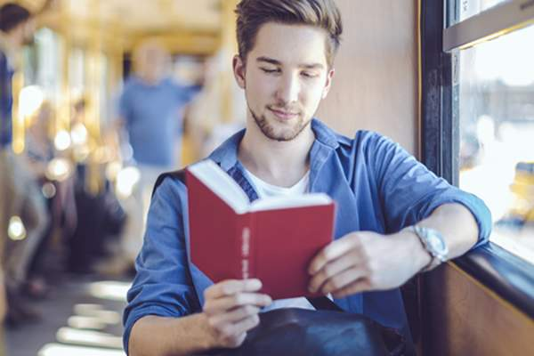 man reading book on bus image