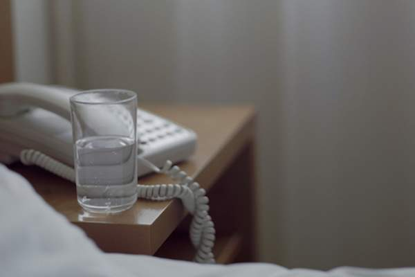 Glass of water on nightstand.