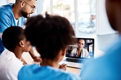 group of doctors talking to another doctor over video chat