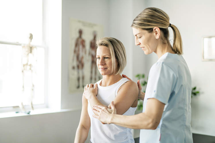 Physical therapist examining a patient's joints
