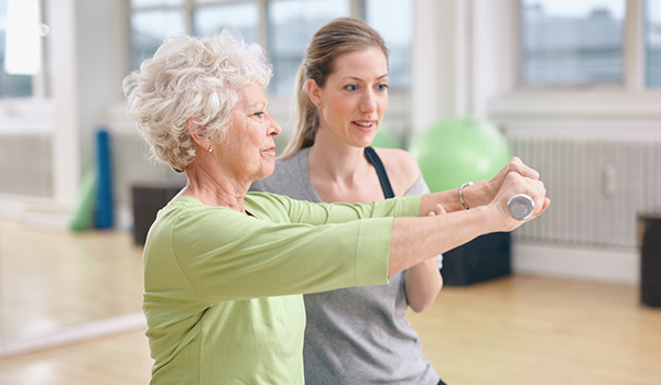 Senior woman working out with a trainer.