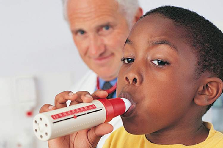 boy using a spirometer as part of a pulmonary function test