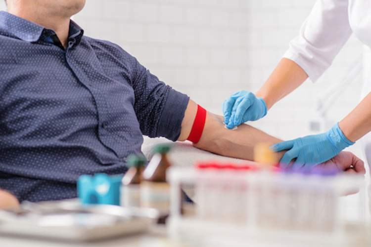 Nurse preparing to draw blood from male patient.