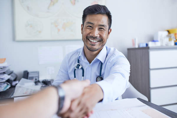 Smiling doctor shaking hands with a patient