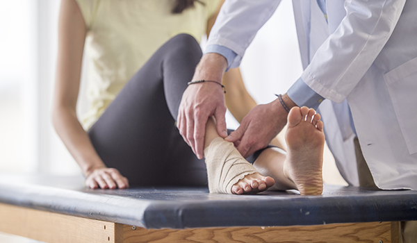 Doctor fixing woman's fractured ankle
