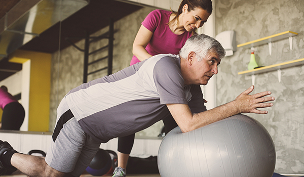 Personal trainer helping senior man on a Pilates ball.