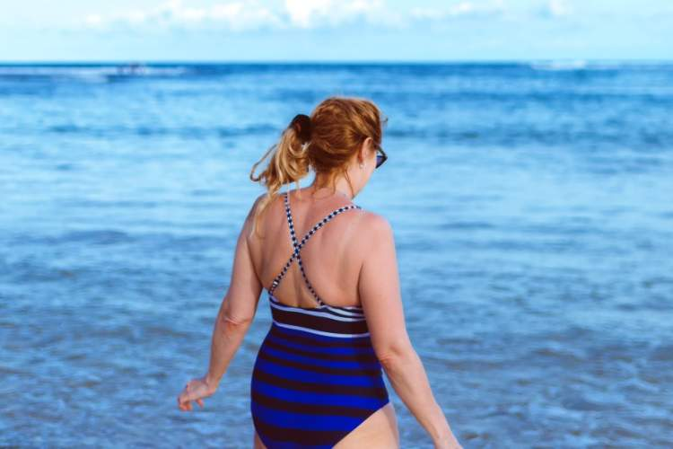 middle-aged woman wearing bathing suit walking into ocean