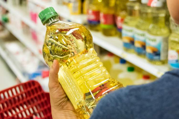 Woman holding bottle of cooking oil in the store.