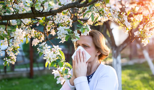 Woman outdoors blowing her nose as she suffers from seasonal allergies.