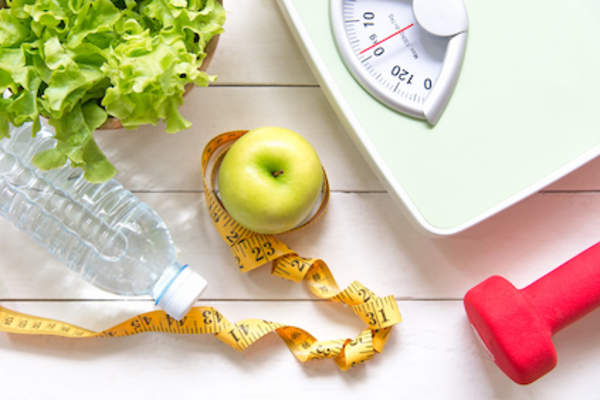 Green apple and weight scale, measure tap with fresh vegetable, clean water and sport equipment .