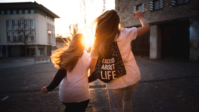 two young woman jumping together, one wearing backpack that reads EXCITED ABOUT LIFE