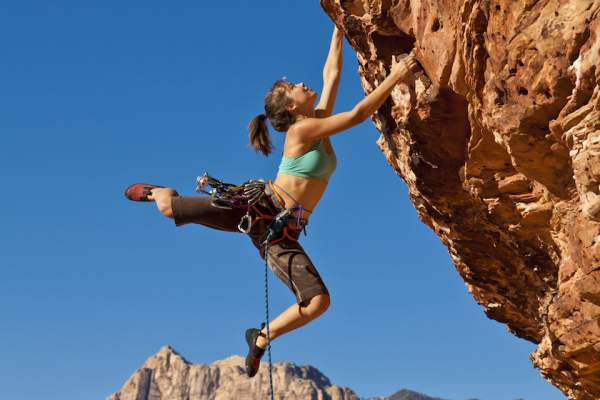 Female rock climber, never give up concept.