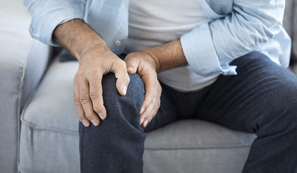 Man with knee pain holding his knee.