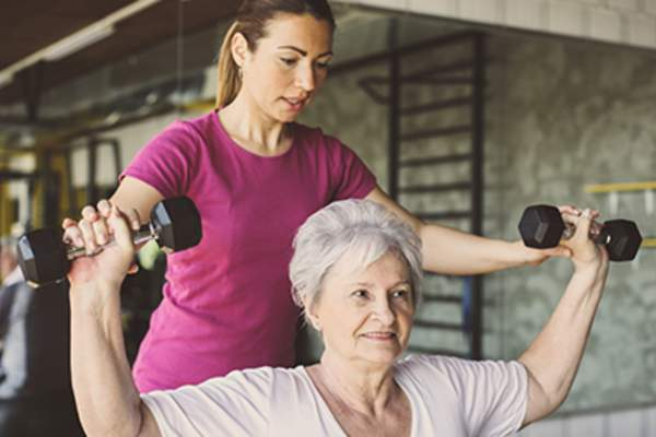 Senior woman exercising with a fitness trainer.