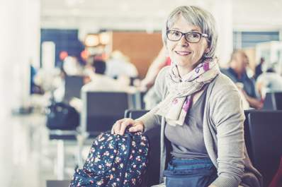 Middle aged woman traveling, waiting in terminal.